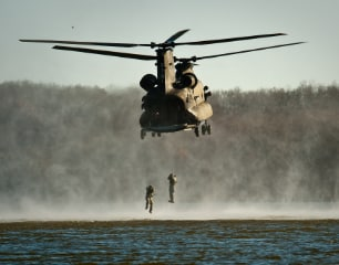 Military helicopter lifting two military personnel
